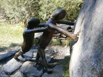 Deux personnes en bronze et en granit font tourner une lourde pierre sur le pont et vers la rivière.